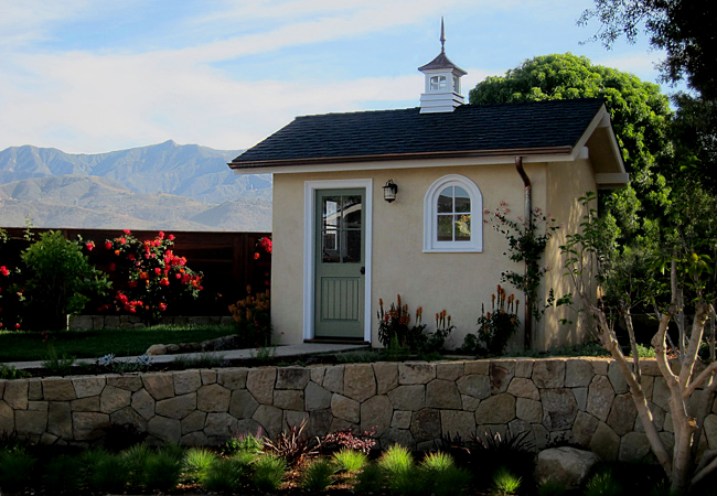 Quality She Shed structure with plaster exterior, wood windows and cupola, copper gutters