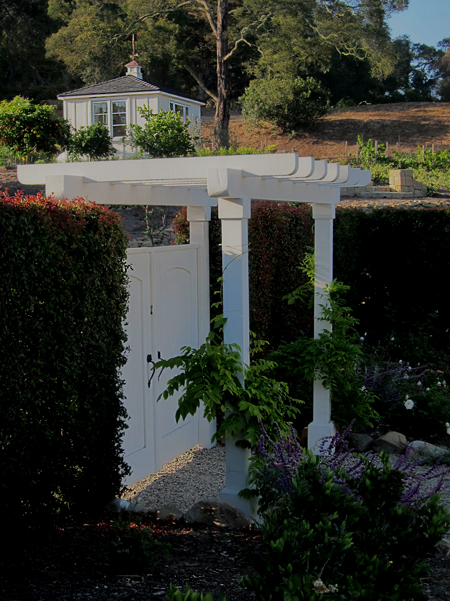 Santa Barbara style landscaping with arbors, garden sheds, gravel, grape vines